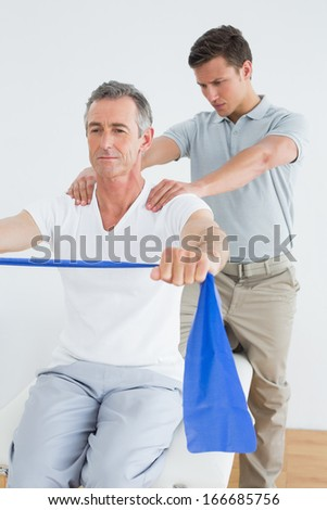 Male therapist massaging mans shoulder in the gym at hospital - stock photo