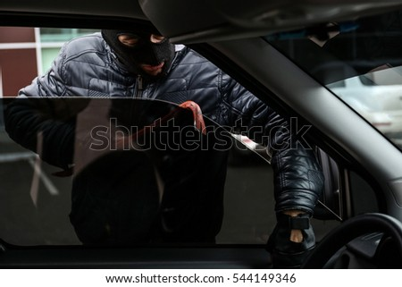 Male thief getting into car through window