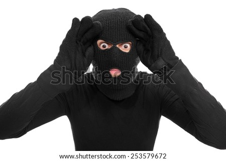 Male thief looking through an imaginary window isolated on white background - stock photo