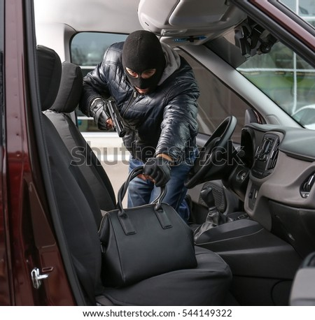 Male thief stealing bag from car seat
