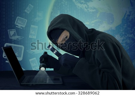 Male thief wearing mask and staring at the camera while using flashlight and magnifying glass to steal information on the laptop - stock photo