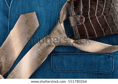 Male tie and wallet lying on denim suit. View from above