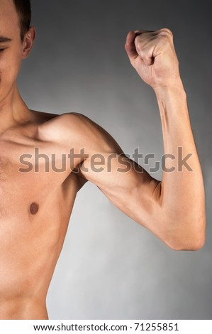 Male torso and arm. Studio shot on gray background - stock photo