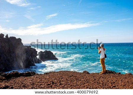 Male tourist photographing on the volcanic coast Los Hervideros on Lanzarote island in Spain - stock photo
