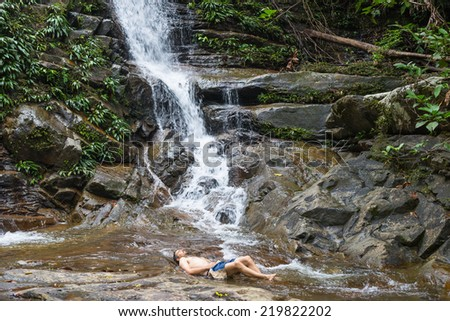 Male tourist relaxing at the beautiful waterfall in the rainforest of Kubah National Park, West sarawak, Borneo, Malaysia. - stock photo