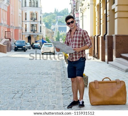 Male tourist standing on the sidewalk of an urban street with a suitcase and map trying tofind directions - stock photo