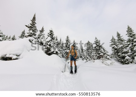 Male tourist with a backpack, with a naked torso and legs is among the snowdrifts and trees.