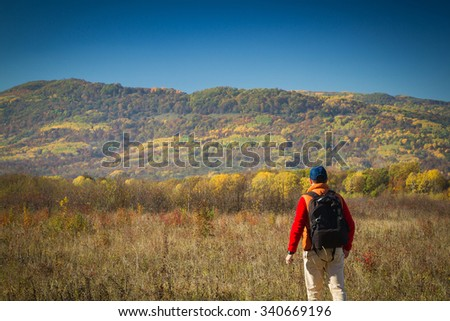 Male tourist with backpack sotret on the horizon in the autumn in the mountains.