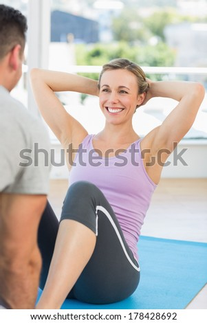 Male trainer assisting woman in doing sits up in fitness studio - stock photo