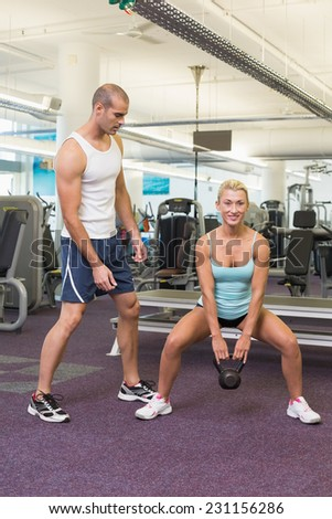 Male trainer assisting woman with kettle bell in the gym