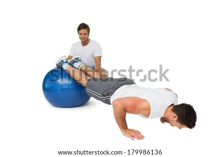 Male trainer helping young man exercise on fitness ball over white background