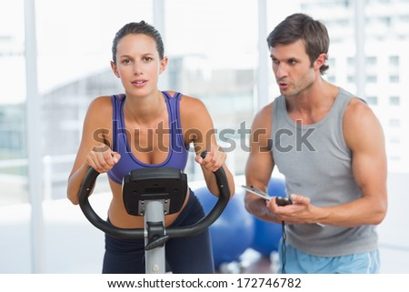 Male trainer watching woman work out at class in gym - stock photo