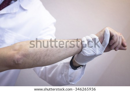 Male Traumatologist orthopedics surgeon doctor examining middle aged man patient to determine injury, pain, mobility and to diagnose medical treatment in shoulder, arm, elbow and wrist.
