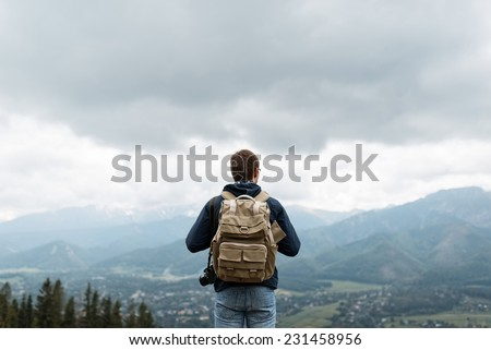 Male traveler from back in the mountains - stock photo