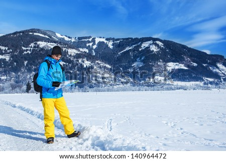 Male traveler in winter clothing hiking with a map