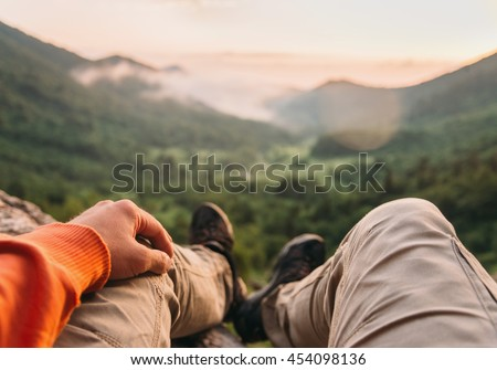 Male traveler sitting in summer mountains at sunset, point of view shot - stock photo