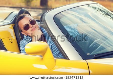Male trendy model posing in yellow convertible car. Sunglasses. checkered shirt - stock photo