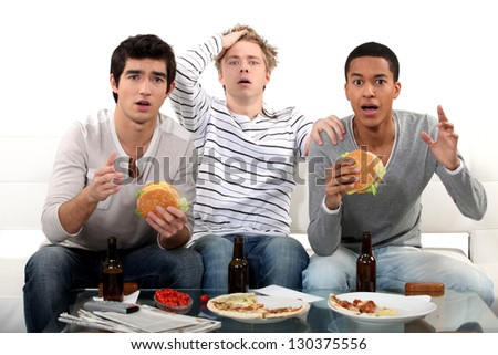 male trio watching soccer match on TV and eating hamburgers - stock photo