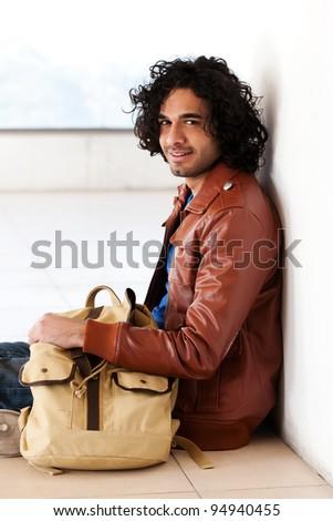 male university student sitting alone corridor - stock photo