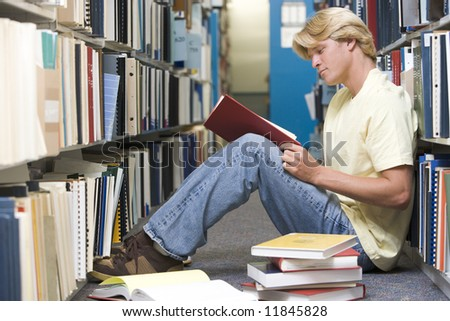 Male university student sitting on floor surrounded by books - stock photo