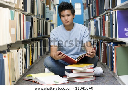 Male university student sitting on library floor surrounded by books - stock photo