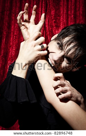Male vampire is biting into a female's arm - stock photo