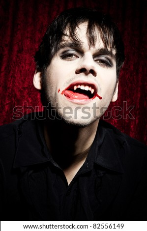 Male vampire licking his bloody lips - stock photo