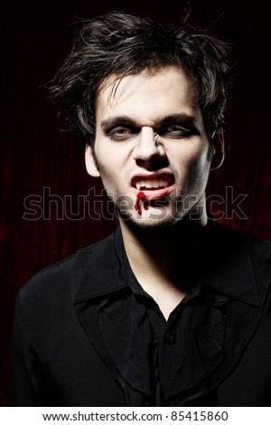 Male vampire showing his teeth - stock photo