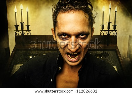 Male vampire with evil eyes opening mouth - stock photo