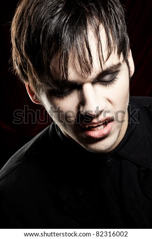 Male vampire with fangs looking down - stock photo