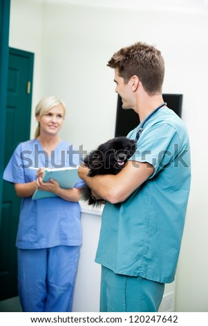 Male veterinarian doctor with a dog looking at female nurse holding clipboard - stock photo