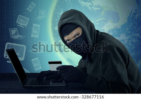 Male villain wearing mask and staring at the camera while stealing credit card identity with notebook computer - stock photo
