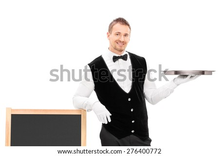 Male waiter holding an empty tray and leaning on a blackboard isolated on white background - stock photo
