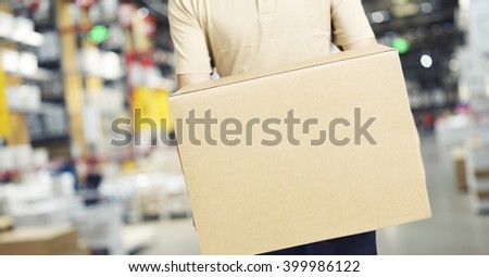 male warehouse worker carrying a carton box of goods in a cash & carry wholesale store. - stock photo