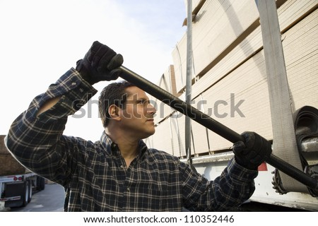 Male warehouse worker loading wood on a trailer - stock photo