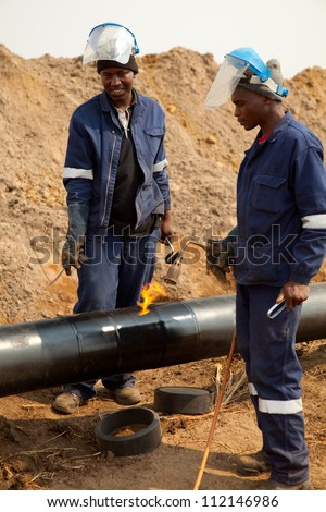 Male welder worker wearing protective clothing fixing welding and wrapping industrial construction oil and gas or water and sewerage plumbing pipeline outside on site