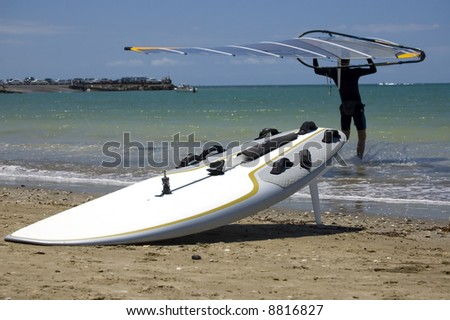 Male windsurfer carrying a sail into the water, surf board at the water edge close-up. - stock photo