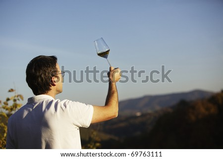 Male winemaker holding up glass of wine for checking consistency of his creation with landscape of hills and blue sky in background. - stock photo