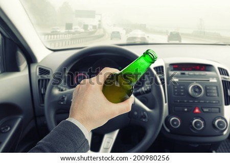 Male with bottle of beer while driving car - stock photo