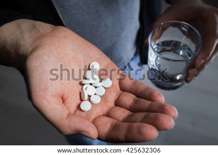 Male with white pills in hand and glass of water - stock photo