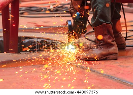 Male  worker wearing protective clothing and repair grinding industrial construction oil and gas or  storage tank inside confined spaces. - stock photo