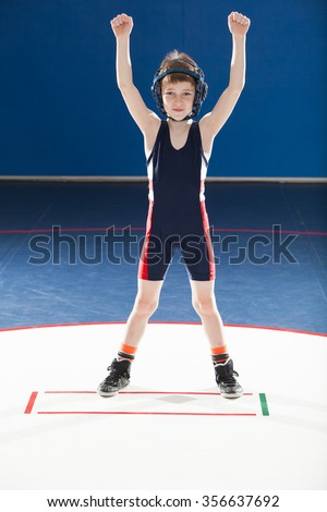 Male youth wrestler with arms up in victory