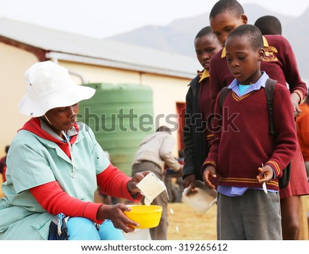 Malealea, Lesotho - August, 27th, 2015: local school; teacher handing out some food. - stock photo