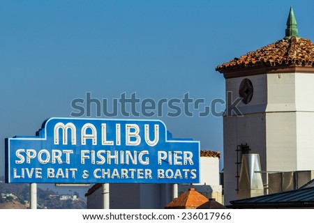 "Malibu Famous Sign 2. Iconic sign marking the Malibu Pier, along the Pacific Coast Highway in southern California. ""Malibu sport fishing pier, live bait & charter boats"". - stock photo"