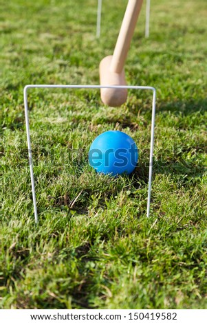 mallet and blue ball in game of croquet on green lawn in summer day - stock photo