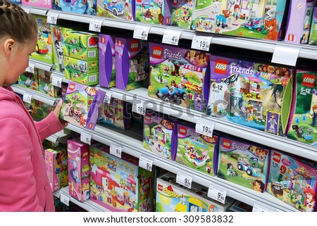 MALMEDY, BELGIUM - JULY 27: Girl select Lego in toy section of a Carrefour Hypermarket. Lego is a popular line of construction toys manufactured by the Lego Group. taken on July 27, 2015 in Belgium - stock photo