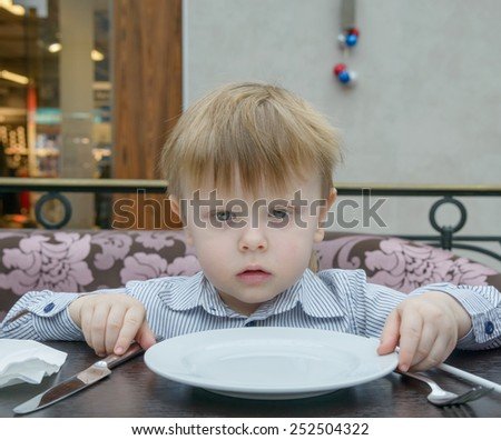 malnnnky boy sitting at a table with an empty plate waiting - stock photo