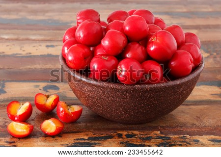Malpighia glabra (red acerola), tropical fruit  on wooden table. Selective focus - stock photo