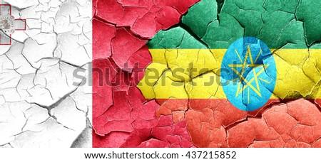Malta flag with Ethiopia flag on a grunge cracked wall - stock photo