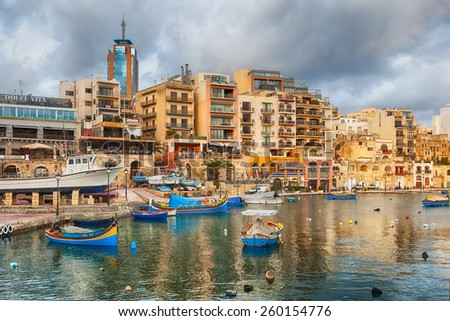 MALTA - JANUARY 23 2015: Spinola Bay with boats in front of famous touristic restaurants and Portomaso tower at back at St Julian, Malta - stock photo